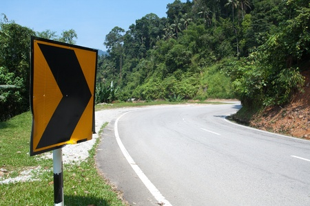 Right arrow Street sign around the of mountain road bend in Cameron Highlands, Malaysia photo