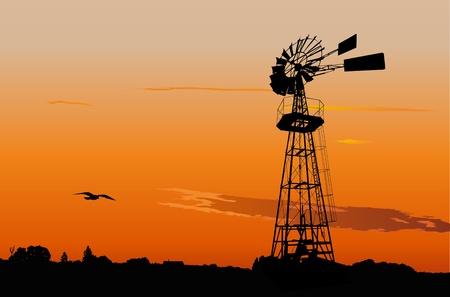 Silhouette d'un moulin à vent de l'eau de pompage millésime contre le coucher du soleil ciel