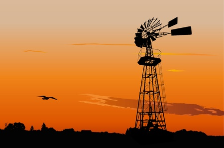 Silhouette of a vintage water pumping windmill against sunset sky
