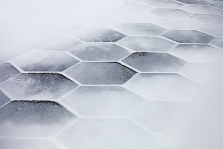 cobble: Hexagonal sidewalk tiles covered with snow and ice
