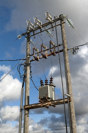 isolator insulator: Electric transformer substation against a blue sky with white clouds Stock Photo