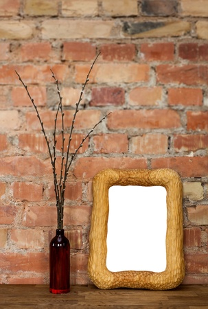 Carved wooden photo frame and brown clay bottle with willow catkins against red brick wall photo