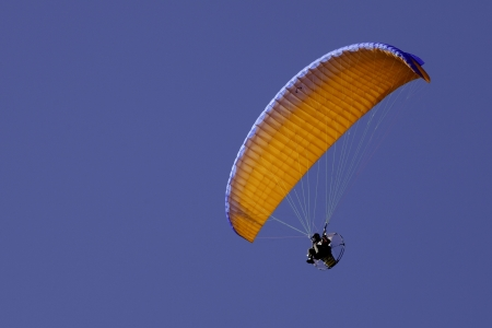 high powered: Orange powered paraglide or paramotor against blue sky