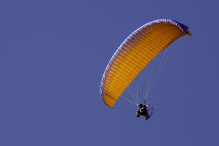 Orange powered paraglide or paramotor against blue sky
