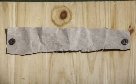 Piece of torn grey recycled paper attached by rusty push pins to wooden wall  Place for short text or headline  photo