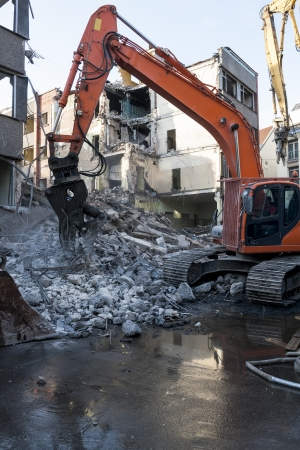 dismantling: Demolition of an old building with heavy machinery for new construction