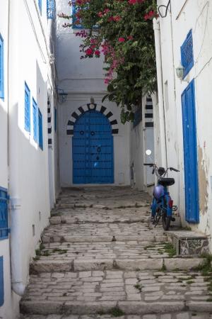 Narrow street with moped in Sidi Bou Said, Tunisia photo