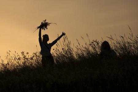 Silhouetten van gelukkige meisje bloemen plukken tijdens midzomer soltice celebraton tegen de achtergrond van de ondergaande zon