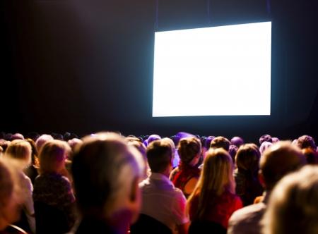 Crowd audience in dark looking at bright screen
