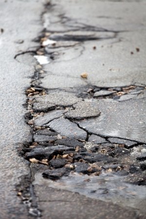 rough road: Damaged asphalt pavement road with potholes caused by freeze and thaw cycle during winter  Stock Photo