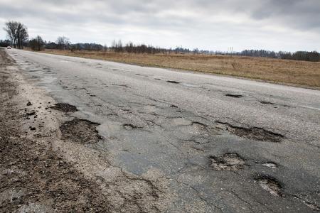 pot hole: Badly damaged country asphalt road