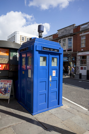 tube station: LONDON - JUNE 11, 2014: Public call police box with mounted a modern surveillance camera near Earls Court tube station in London.