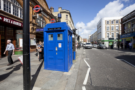 emergency call: LONDON - JUNE 11, 2014: Public call police box with mounted a modern surveillance camera near Earls Court tube station in London.