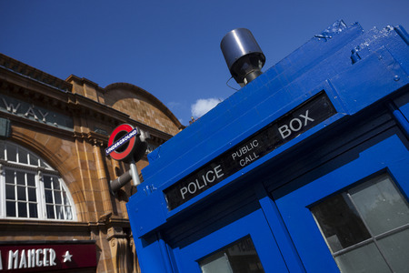 who: LONDON - JUNE 11, 2014: Public call police box with mounted a modern surveillance camera near Earls Court tube station in London.