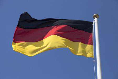 official symbol: Germany flag flying in the wind, deep blue sky