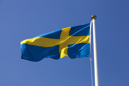schweden flagge: Schweden-Flagge fliegen in den Wind, tiefblauen Himmel Lizenzfreie Bilder