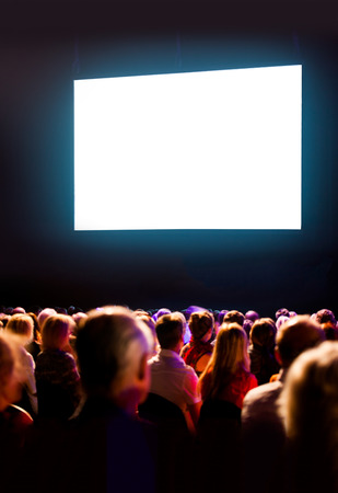 theater audience: Crowd audience in dark looking at bright screen