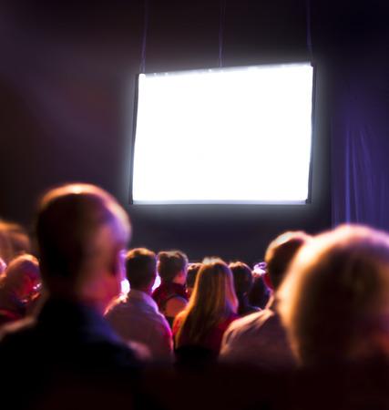 spectator: Crowd audience in dark looking at bright screen