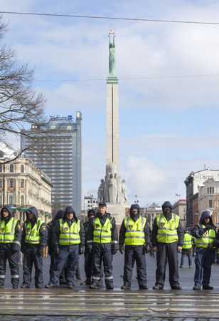 police unit: RIGA, LATVIA - MARCH 16, 2014: Police line infront Freedom Monument ready to prevent provocations at Commemoration of Latvian Legion (Waffen SS) unit. Event is drawing crowds of nationalists & antifascist demonstrators.