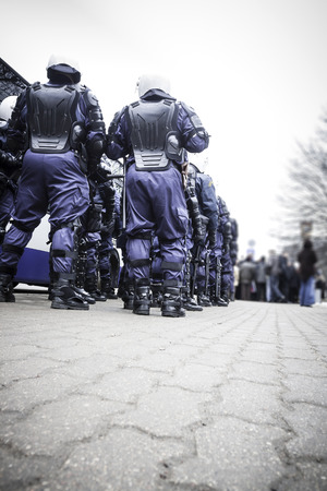 riot: Unit of police special forces in riot gear waiting for orders.