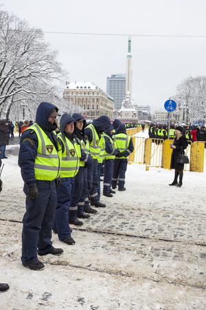 quell: RIGA, LATVIA, MARCH 16, 2010: Local police guard cordon behind crowd control barriers at the Freedom Monument at the commemoration of the Latvian Waffen SS unit. Editorial