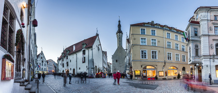 europe travel: Crowded Tallinn Old town streets with Town Hall in the evening. Panoramic montage from 7 HDR images. Long exposure with motion blur