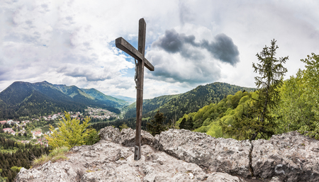 baile: Panoramic view of Romanian town Baile Tusnad in Carpathian mountains from cliff with large wooden cross