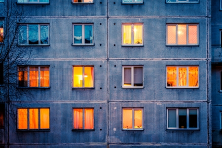 Wall with Iluminated windows. Detail of soviet era block apartment building