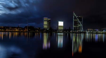 Riga skyline with some skyscrapers. Night shot with scenic water reflections in Daugava river waters