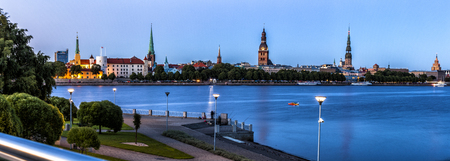 Traditional Riga skyline with Riga Castle and many churches as seen over Daugava river during blue hour. Stock Photo