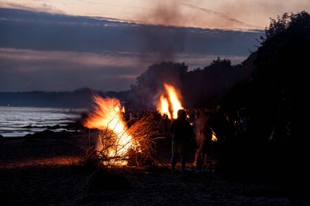 Unrecognisable people celebrating summer solstice with large bonfires on Baltic Sea sandy beach Stockfoto