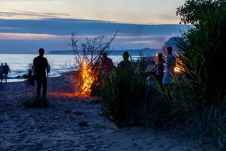 Large crowd of unrecognisable people celebrating summer solstice with large bonfires on Baltic Sea sandy beach