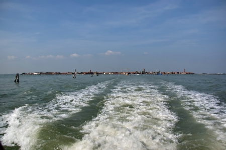 Murano island view a distance from one boat in the lagoon, Venice, Italy  photo