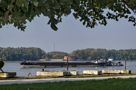 cement chimney: Tugboat with ship pass along the riverside park in Ruse town, Bulgaria