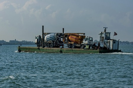 truck concrete mixer: One load flat-boat ferry two concrete mixer truck via the lagoon, Italy