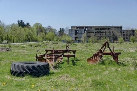 farm machinery: Abandoned unfinished building and farm machinery, Bulgaria Stock Photo