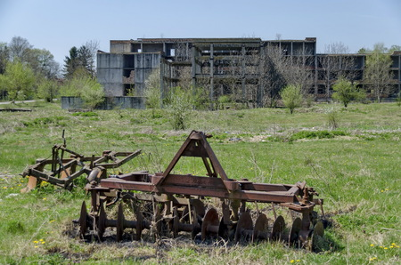 unfinished building: Abandoned unfinished building and farm machinery, Bulgaria Archivio Fotografico