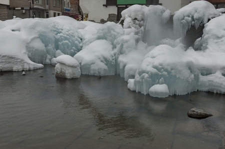 vapour: Ice figure with snow hat in mineral water lake, Bansko town
