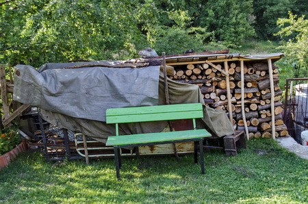 repose: Stack dry firewood and bench in small courtyard