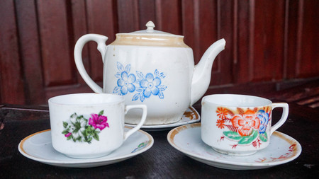 china porcelain teapot with flower pattern and white glass on the old house terrace in indonesia - asian Reklamní fotografie