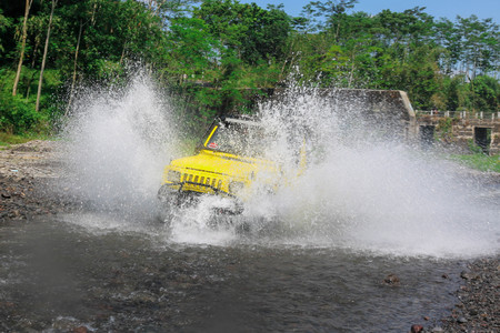 Extreme offroad car through water on the river so as to create sparks at Merapi Mountain Yogyakarta - Indonesia, Asia