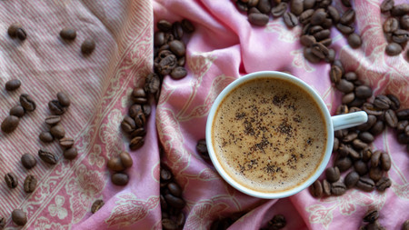 White coffee cup and coffee beans around it with traditional fabric background Reklamní fotografie