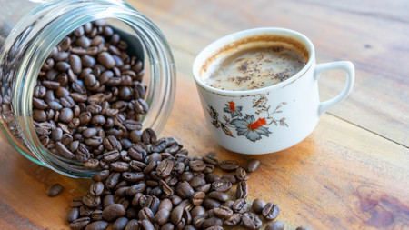 White coffee cups and coffee beans that spill around with wooden table backgrounds