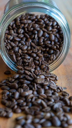 coffee beans spilled against a wooden table background Reklamní fotografie