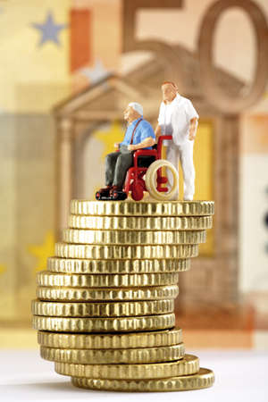 Figurine in wheelchair and caregiver on pile of coins