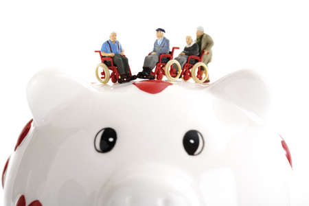 foresight: Figurines in wheelchairs on piggy bank LANG_EVOIMAGES
