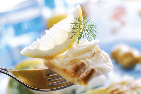 food: Codfish with dill and lemon slice on fork LANG_EVOIMAGES