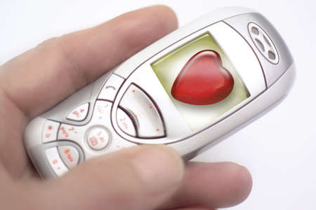 Mobile phone displaying heart shape symbol,close-up LANG_EVOIMAGES