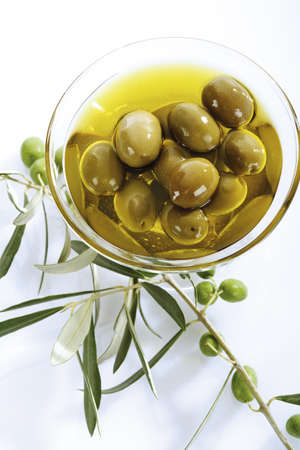birdseye: Fresh green olives and olive oil in glass bowl
