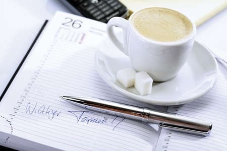 noting: Cup of coffee on a diary, ball-point in front
